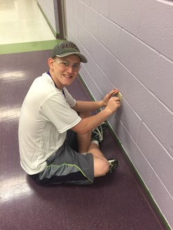 A Student of the Summer Maintenance Program replaces an outlet cover at BRJH