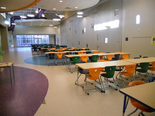 photo of cafeteria with tables and chairs ready to serve students.