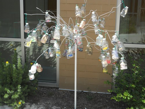 photo of bottle creation hanging like a tree in the courtyard.