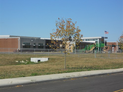 front outside view of school with large playground.