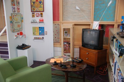 photo of chair, television with vintage Atari video game system with other games on wall.