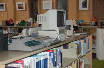 photo of many old typewriters and a desk top computer.