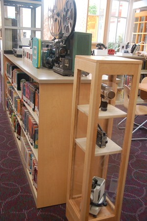 photo of display of antique movie projector and hand held movie cameras.