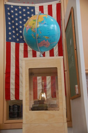 photo upclose of world glove on display with books and hand bell with american flag hanging behind.