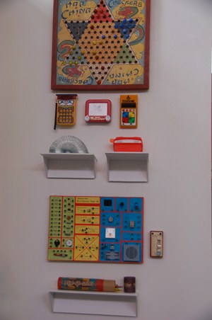 photo of close up view of vintage games and trinkets displayed on wall.