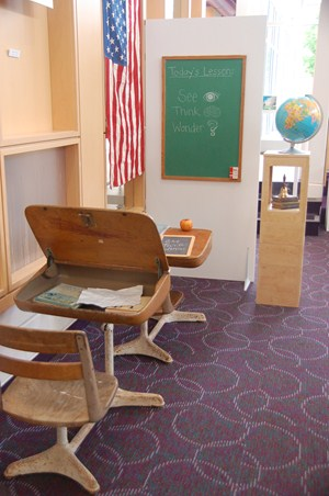 photo of vintage school room set up with wood desks, chalkboard, globe and bell.