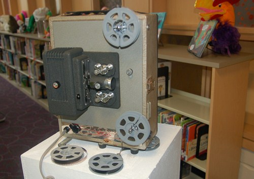 photo of silent movie projector with film reels.