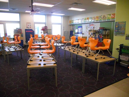 photo of chairs stacked on tables in kindergarten classroom