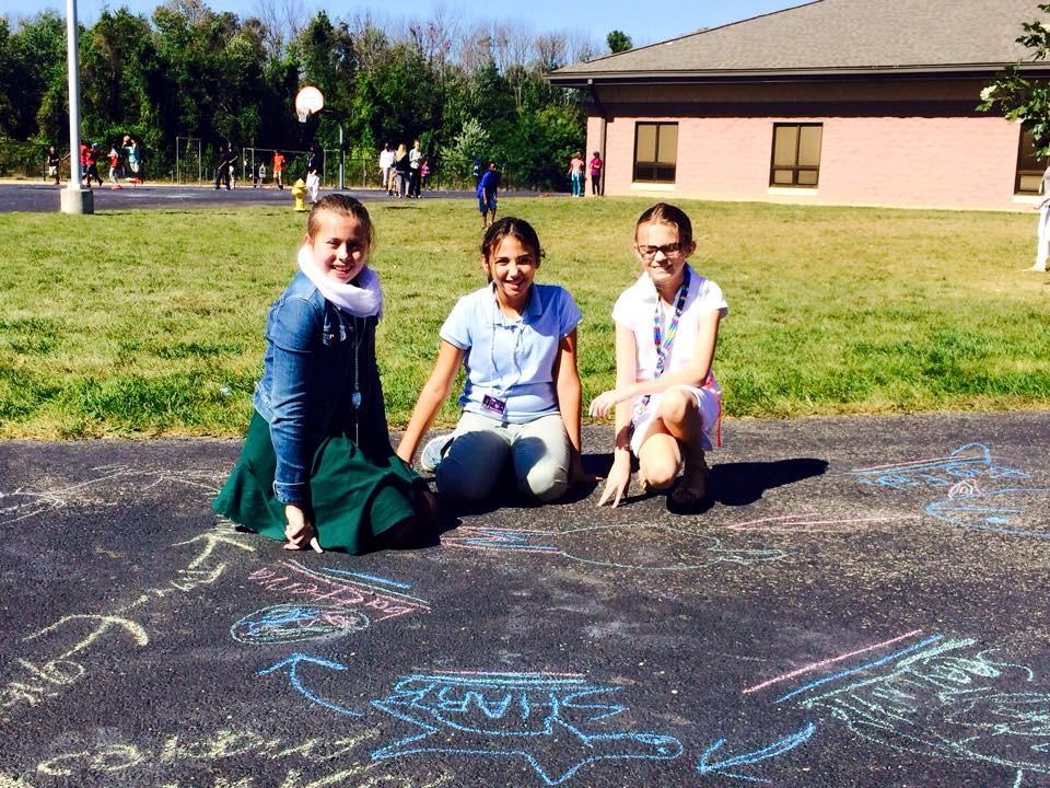 Students working with sidewalk chalk