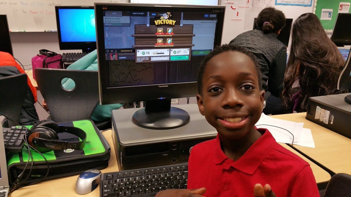 Student smiling in front of computer