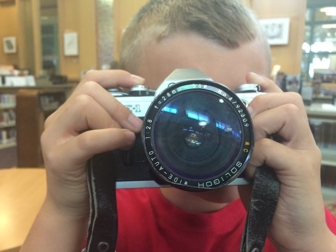 photo of student look directly at us through the lens of a large photo camera.