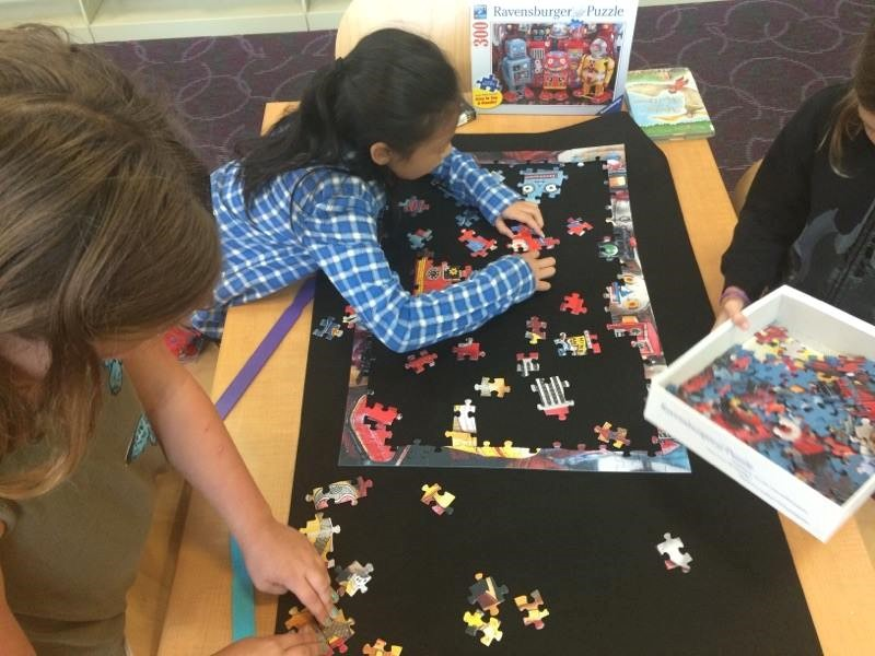 photo of students working on putting a puzzle together.