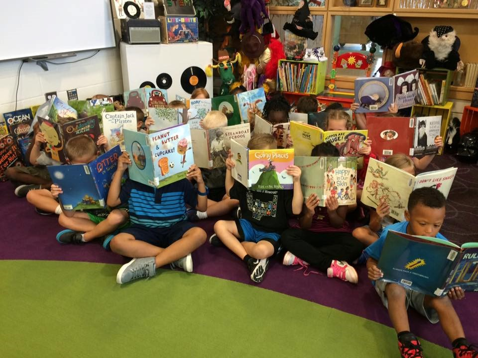 photo of large group of student reading books who are hiding their faces.