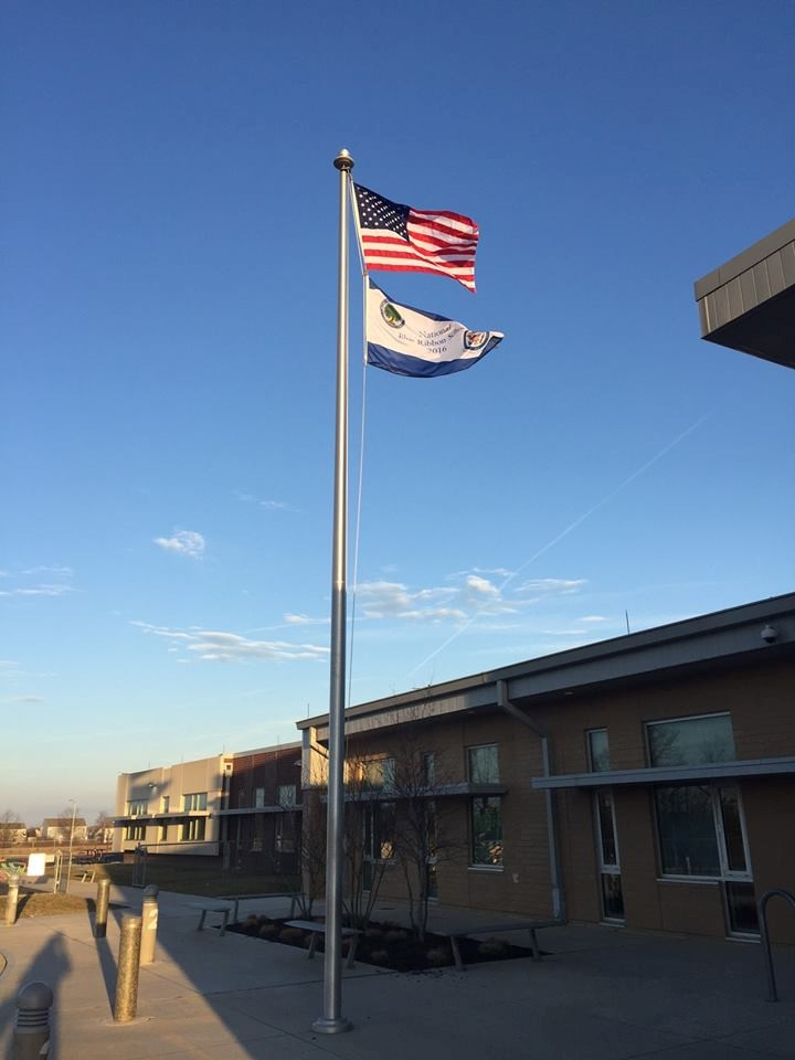 flag pole with american flag and 2016 national blue ribbon school flag waving from the pole.