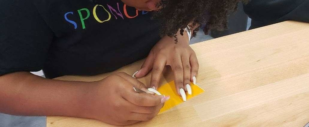 A student is working to pick the white space out of her yellow vinyl sticker.