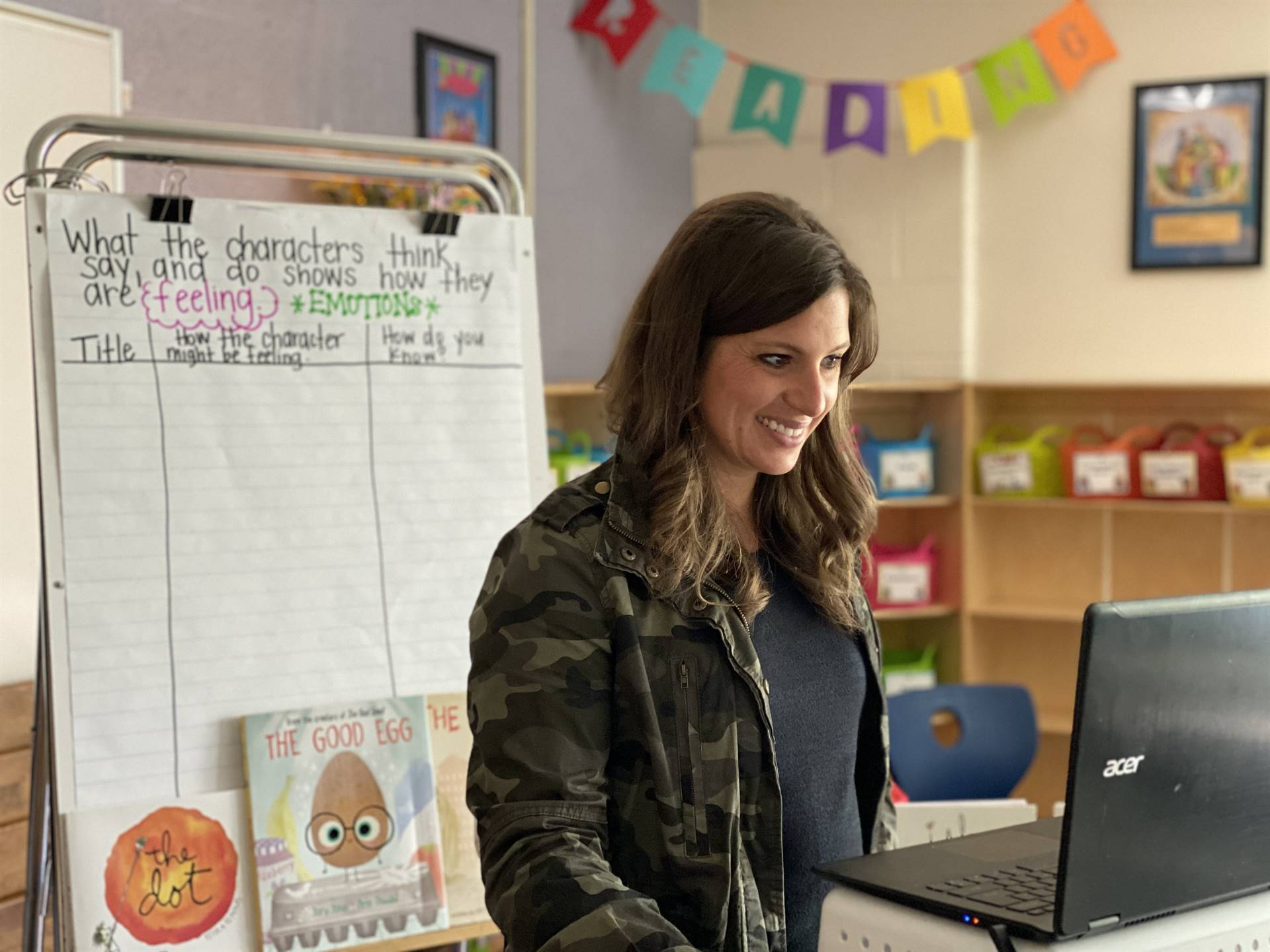 Teacher with chromebook with chart behind.