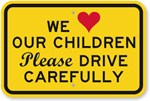 "street sign stating ""we love our children please drive carefully"""