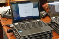 Stack of Chromebooks on a conference table.